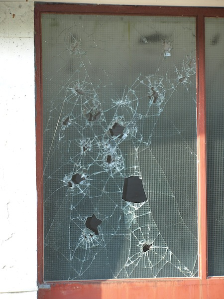 Window with bullet holes.