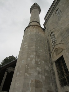 Patched shrapnel or bullet splats on mosque minaret.