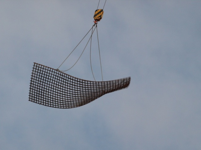 Steel reinforcing sheet being lifted into position on a building site.