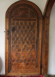 Intricate wooden door opening into the lounge area.