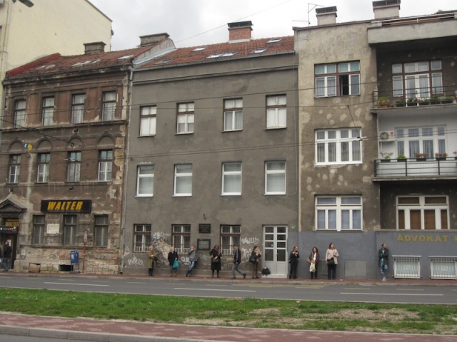 Workers waiting for a bus in Sarajevo. Note the patched bullet holes in the wall (building second from the right).