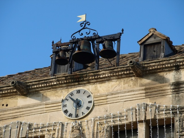 Bells mounted on the roof of the town hall. Note the cannon-shaped gargoyles, the neat dormer window and the blue sky.