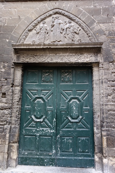 What's behind the green doors? And what is the story depicted in the bas relief above the door?
