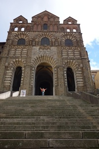 Embracing the stone on the steps of the Roman Catholic Cathédrale Notre-Dame du Puy. It is a national monument of France.
