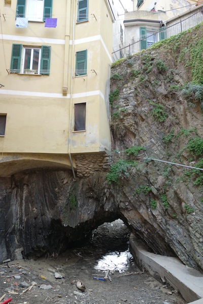 House clinging to a rockface over a creek.
