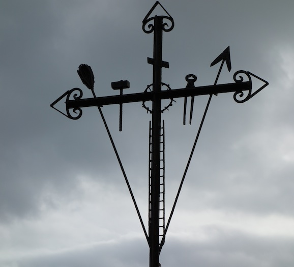 Steel cross with personal touches including, pincers, hammer and a ladder.