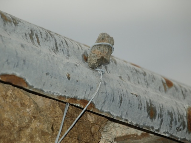 Securing a corrugated iron roof.