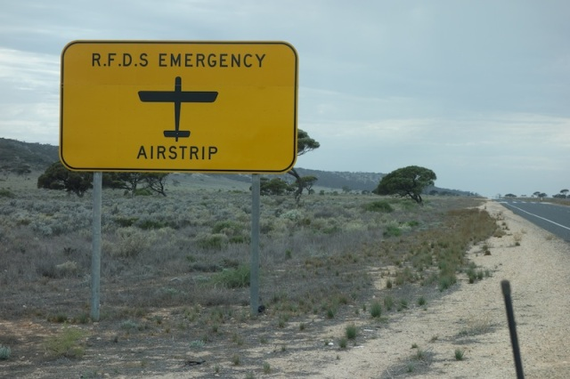 The road across the Nullarbor is used in places as an emergency airstrip. R.F.D.S. stands for Royal Flying Doctor Service.