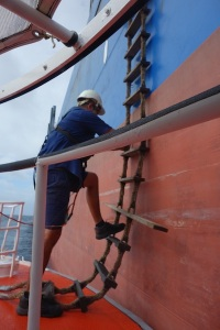 Alongside and the pilot boat deckhand testing the ladder prior to the pilot coming down.