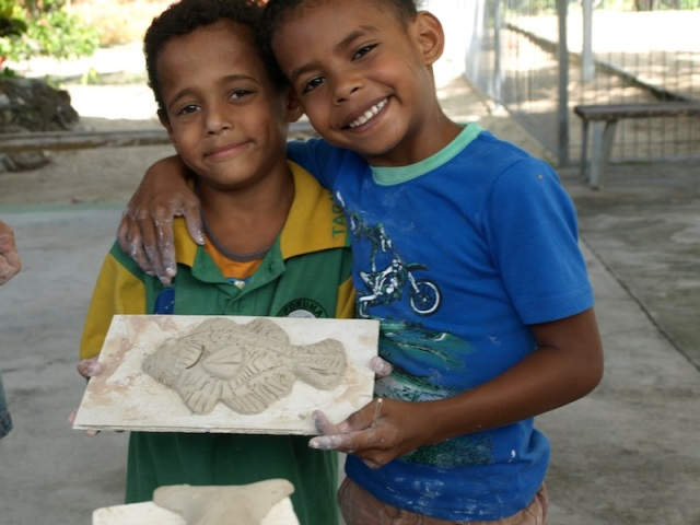Two of the local schoolboys with a fish they made.