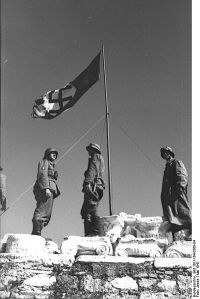 The symbolic beginning of the occupation: German soldiers raising the German flag over the Acropolis. This image was provided to Wikimedia Commons by the German Federal Archive (Deutsches Bundesarchiv).