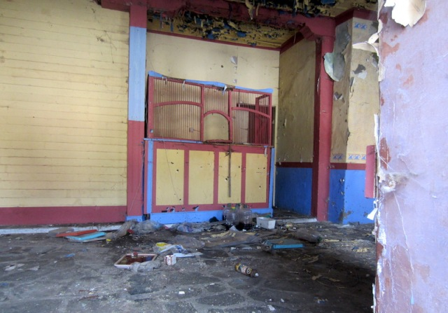 Through the panelled door to a ticket seller's box. The building must have been used as a theatre at one stage.