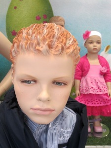 A realistic mannequin face in an exclusive children's wear shop window.