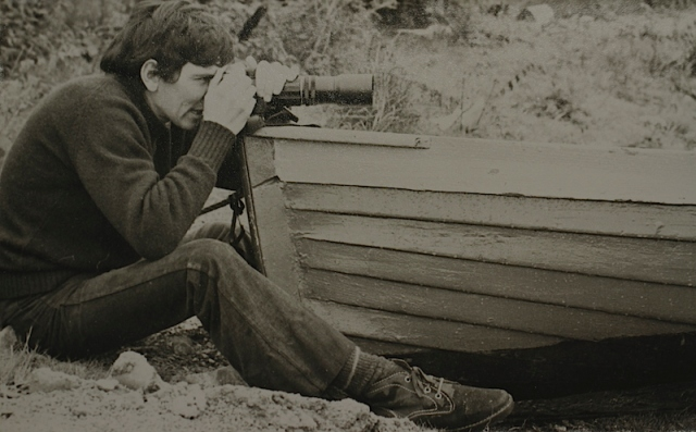 Me steadying my camera on a wooden clinker built boat in Scotland 1973. Desert boots, long hair and flares were the go in the 1970s!