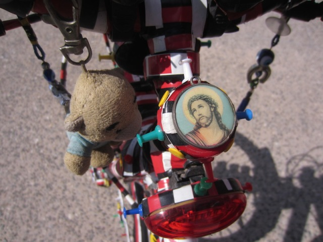 Close up of the bells and whistles bike. Protector Jesus and Tbear's Greek cousin hitching a ride.
