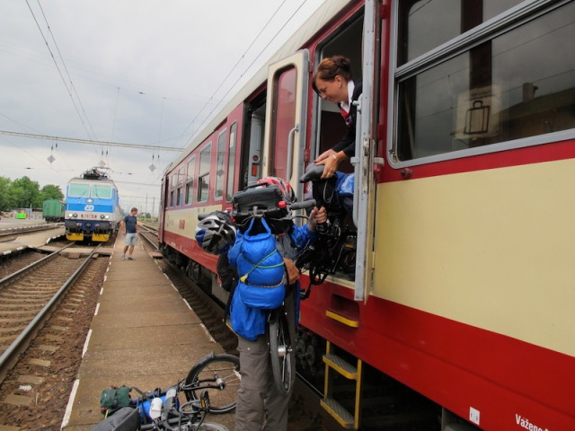 Train attendant passing down one of our bikes on arrival at Melnik.