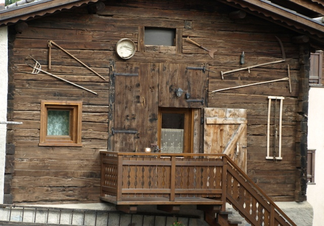 Traditional house of the Livigno area. Farmers' tools of trade consigned to the museum wall.