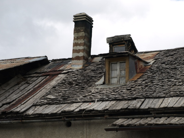 Farmhouse roof. Of interest is the combination of wooden planks and shingles.