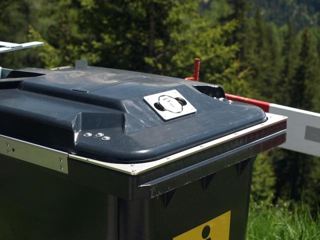 Specially designed bear proof wheelie bin with lock and metal reinforced lip.