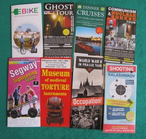 A few of the many Prague tourist brochures, some inviting tourists to explore the dark eras of Prague, fire a Kalashnikov high-powered weapon or command a military tank.