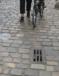 Cobblestones and a nasty grate, not designed for cyclists.  In bike-friendly countries the slots are 'S' shaped.