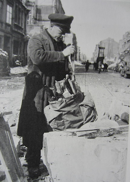 A man collecting firewood from the ruins, a verboten activity. Image from German Achives.