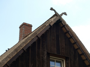 Snakehead finials on the end of a thatched roof house.