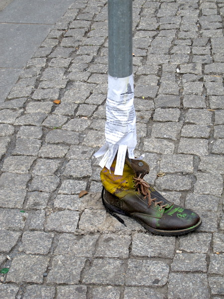 An alternative way of thinking, an eye-catching advertisement on a signpost. The side of the boot had been cut and the boot wrapped around the pole.