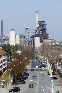 Main street and steel mill.   Photo: Eisenhuttenstadt Weg zum Hochofen 2012 via Wikipedia