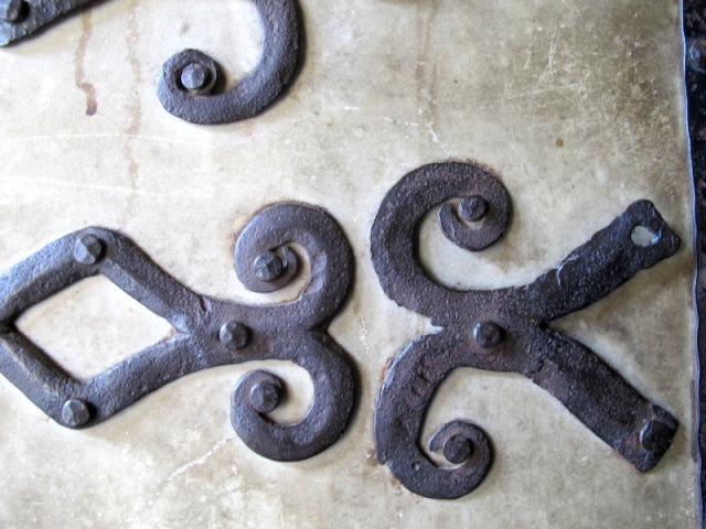 Hinges of a pigskin-covered door on the cathedral. In times when there were no wood stains and preservative coatings covering a wooden door with pigskin makes sense.