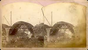 A stereoscopic card showing timber formwork in place and the voussoirs creeping to the apex of the arch. image from minneapolisparkhistory.com