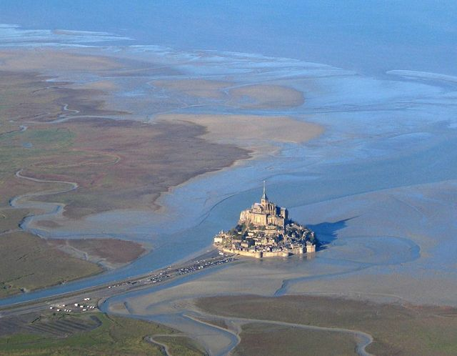 Mont St Michel stuck in a sea of mud. This photograph was taken before the levee-style causeway was replaced with a bridge. Image: Fabos via Wikipedia.