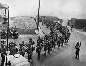 American soldiers, equipped with full pack and an extra allotment of ammunition, march down an English street to their invasion craft for embarkation to Normandy.  Image credit:  AP from http://vcepinc.org