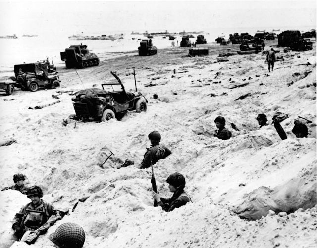 American soldiers sitting in their foxholes. Not much protection, a few buckets of beach sand. Photo by: AP/Weston Hayes via http://vcepinc.org