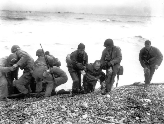 Members of an American landing unit help exhausted comrades ashore. Photo AP via via http://vcepinc.org web page