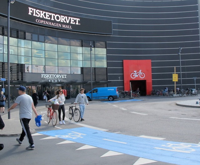 The red door is the entrance to a Copenhagen mall bike storage area and the blue bike path is a no go zone for cars.