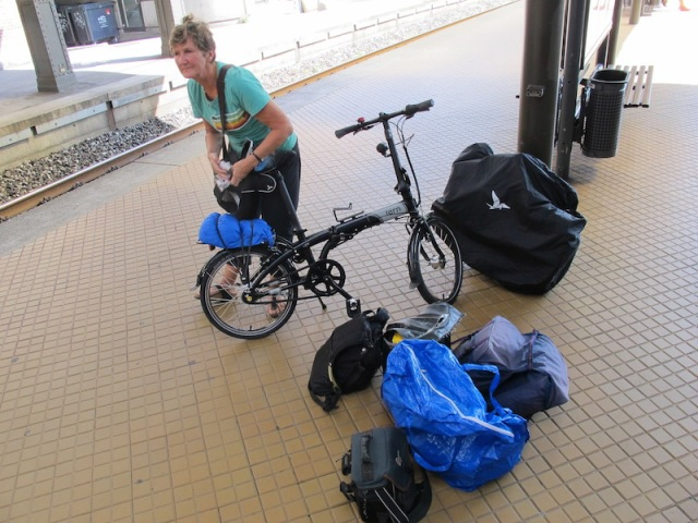 Bev preparing to fold her bike. My bike is folded and in its protective bag leaning against the stanchion.