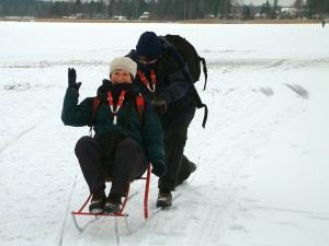 Pushing Bev across the lake in 2006.  The obligatory ice picks are hanging around our necks.