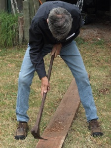Head down and adzing a rough sawn ironbark plank with a long-handled adze.