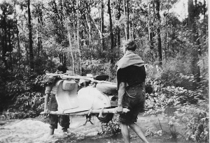 Carrying the Lambretta across a flooded creek.  I may have the light end (the front) but I am walking backwards which was difficult!  Image from John's archives.