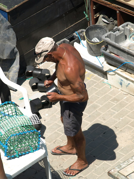 A white/brown fisherman tending his traps in the fishing port.