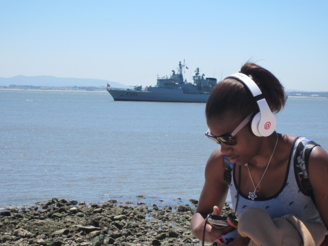 A warship anchored and a lass tuning in near the main square.