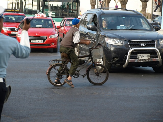 An old bloke playing chicken with Moroccan traffic. The policeman (left) and the passenger in the car abused the bike rider for getting in the way.
