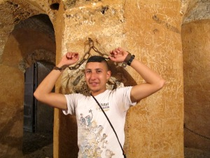 Omar demonstrating prisoner restraint in the dungeon of the Kasbah.