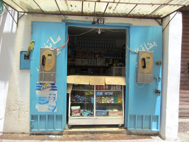 A hole-in-the-wall grocer. Note the two public telephones mounted on the inside of the shop doors.