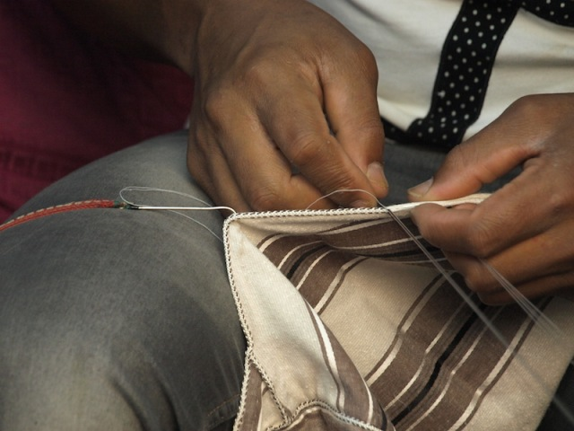 Sewing a cord into the selvedge of a djellaba.