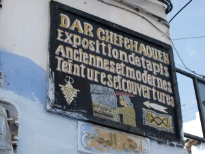 Sign pointing to an exhibition devoted to carpets and tapestries.