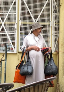 A tout with handbags and purses to sell waiting to pounce.
