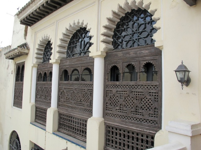 Intricately carved Moorish-style wooden window shutters above the garden.