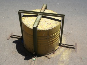 A No Parking deterrent, a half oil drum full of concrete bolted to the road. The drum deterrents extended right along the front of a building.